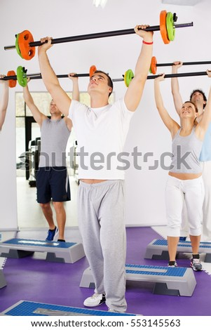 Group of people lifting barbells in weight training class, doing shoulder exercise.