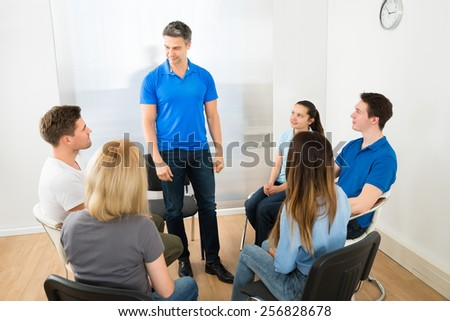 Group Of People Looking At Man Explaining - stock photo