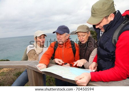 Group of people looking at map on a hiking day - stock photo