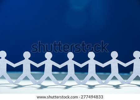 Group of people made of paper are holding hands together. Team concept.