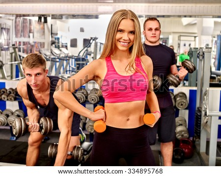 Group of people man and woman working with  dumbbells his body at gym. All people can be seen reflected in a mirror. - stock photo
