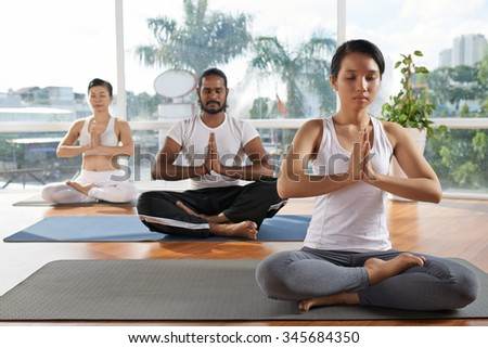 Group of people meditating in yoga class - stock photo