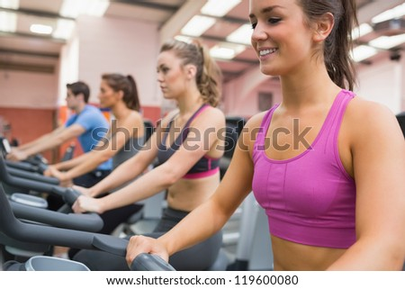 Group of people on exercise bicycles in the gym - stock photo