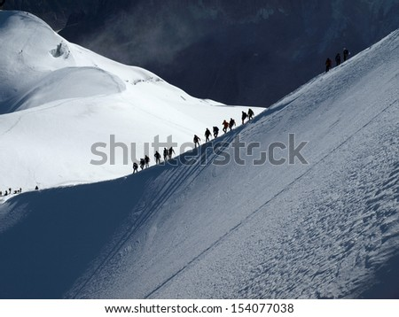 Group of people on snowy path - stock photo
