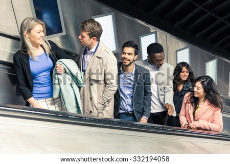 Group of people on the escalator. They are a mixed group of persons, they could be friends or just strangers. Urban lifestyle and transportation concepts. - stock photo
