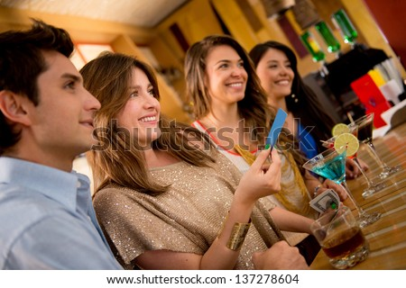 Group of people paying for drinks at the bar and smiling - stock photo