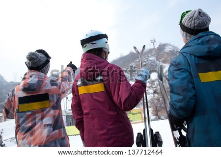 Group of People Pointing at Hill in Ski Resort