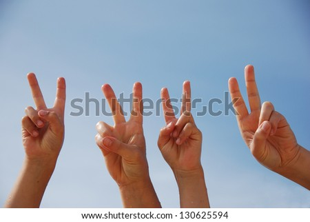 Group of people raise hands in air across blue sky