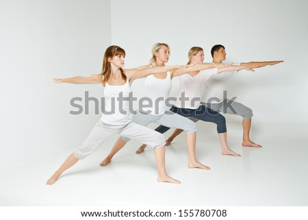 Group of people relaxing and doing yoga in white studio - stock photo