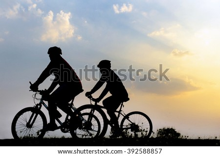 group of people ride bicycle on sunset and lens flare background