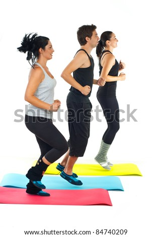 Group of people running on colorful mats in a fitness club - stock photo