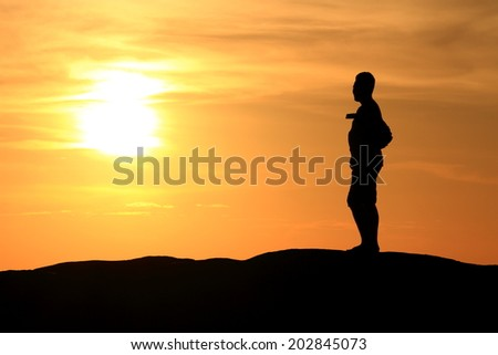 group of people's silhouette on the jetty isolated over sunset and dramatic sky