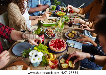 Group of people sitting at festive table and eating - stock photo