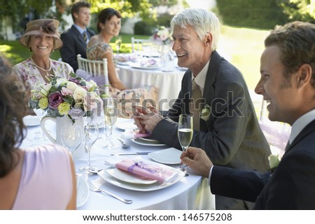 Group of people sitting at wedding tables in garden - stock photo