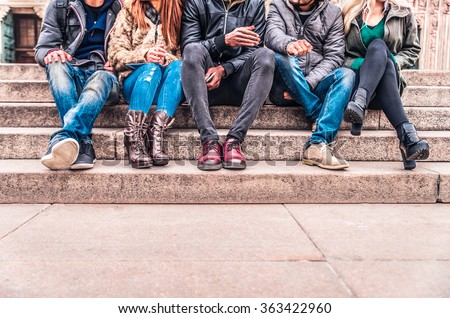 Group of people sitting on a staircase outdoors, close up on low section body - Multiracial friends talking and having fun on a meeting outdoors - stock photo