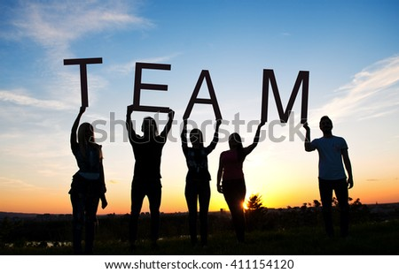 Group of people spelling TEAM, outdoors, sunset  - stock photo