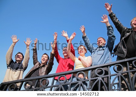 group of people stand with  hands lifted in  greeting - stock photo