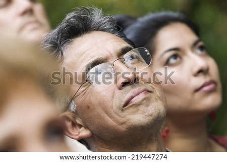 Group of people standing together looking up - stock photo