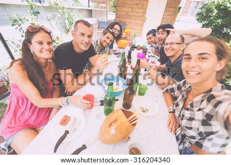 Group of people taking selfie while having lunch outdoor. A multicultural group of friends is taking a selfie while eating. They are happy and there are a lot of plates and bottles on the table. - stock photo