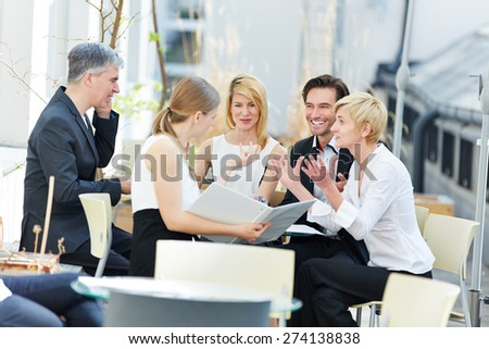 Group of people talking about business outdoors in a coffee shop - stock photo