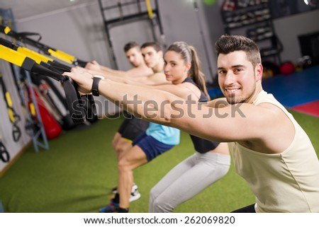 Group of people training elastic rope at gym in cross and fit room - stock photo
