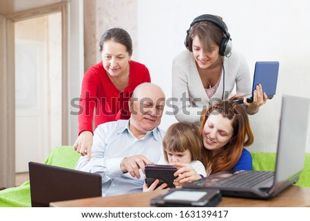 Group of people  uses few various electronic devices in home interior