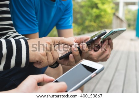 Group of people using smartphone together