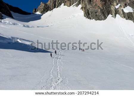 Group of people walking among snows of New Zealand mountains