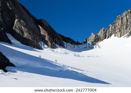 Group of people walking among snows of New Zealand mountains - stock photo