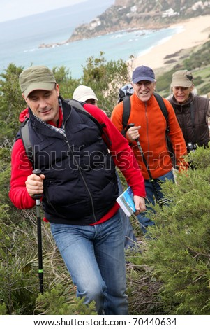 Group of people walking in natural landscape - stock photo