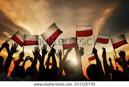 Group of People Waving Polish Flags in Back Lit - stock photo