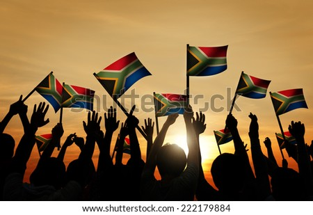 Group of People Waving South African Flags in Back Lit - stock photo