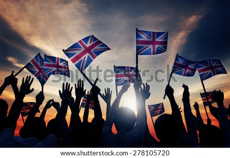 Group of People Waving UK Flags in Back Lit - stock photo