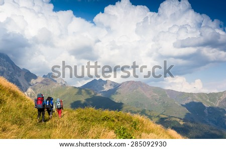 group of people with backpacks walking on the trail - stock photo