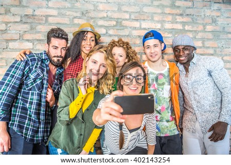 Group of people with colorful trendy clothes bonding together and having fun - Young cheerful friends taking a selfie - stock photo