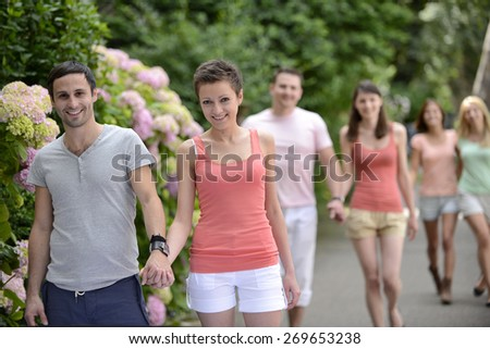 Group of people with couples walking outdoors on a beautiful spring or summer day - stock photo