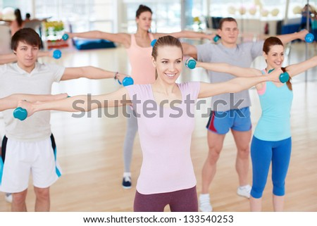 Group of people with dumbbells indoors