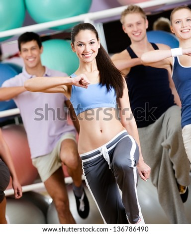 Group of people with perfect figures exercise at the gym in a fitness class - stock photo