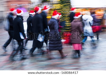 group of people with Santa Claus hats walking on a christmas market in motion blur