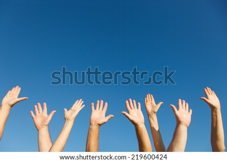 Group of people with their arms raised. - stock photo