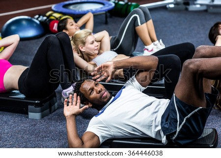 Group of people working their abs in gym - stock photo
