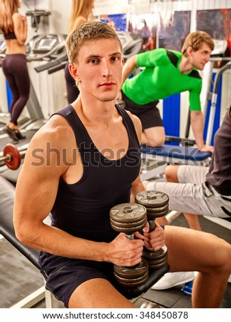 Group of people working with  dumbbells his body at gym. Portrait of handsome man. - stock photo