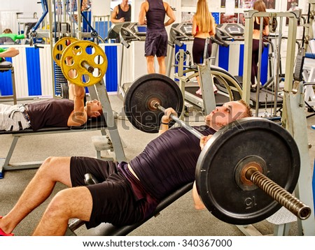 Group of people working with  dumbbells his body at gym. Strong man in the foreground. - stock photo