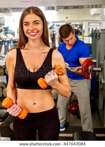 Group of people working with dumbbells his body at gym. Woman work with small dumbbells man works with big dumbbells. - stock photo
