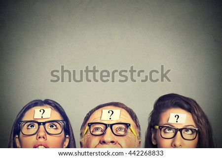 Group of people young women senior man with question mark looking up isolated on gray wall background with blank copy space above head