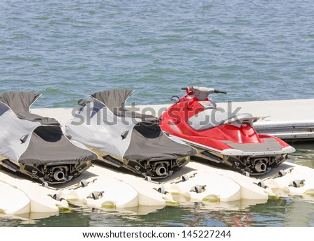 Group of personal water craft, jet skis at the dock. Bright red jet ski next to 2 covered jet skis docked at the marina in calm blue water. Rear view showing the jet nozzle. Horizontal view. - stock photo