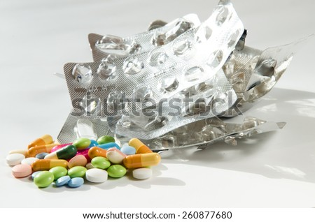 group of pills and silver empty pills blister isolated - stock photo