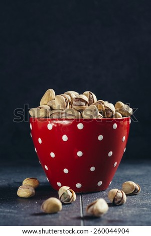 Group of pistachios in the red dotted cup,selective focus and blank space - stock photo