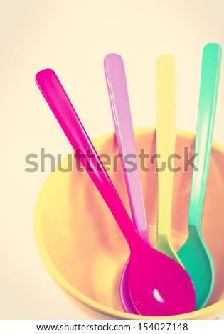 Group of plastic spoons in yellow bowl with retro filter effect - stock photo
