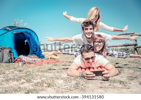 Group of playful friends having fun in a campsite during an open-air concert event - Young cheerful people taking a selfie on a summer holiday in the nature - stock photo